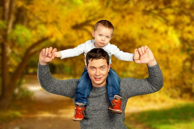 Młody ojciec i jego uśmiechnięty syn ściska czas i cieszy się razem, świętowania dnia ojca Premium Zdjęcia
