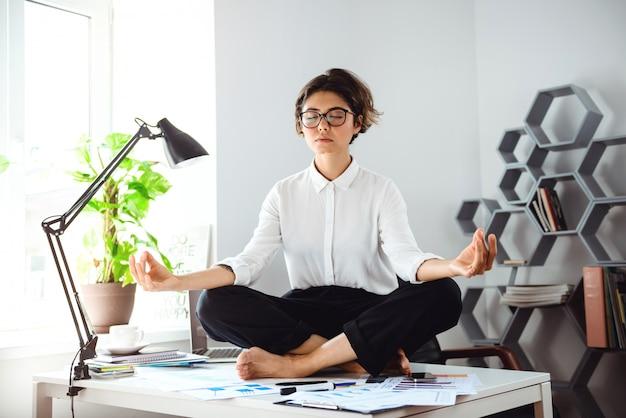 Młody Piękny Bizneswoman Medytuje Na Stole Przy Miejscem Pracy W Biurze. Darmowe Zdjęcia