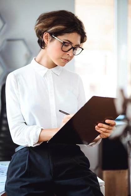 Młody Piękny Bizneswoman Pisze Falcówce Przy Miejscem Pracy W Biurze. Darmowe Zdjęcia