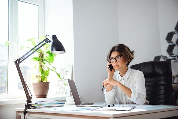 Młody Piękny Bizneswomanu Mówienie Na Telefonie Przy Miejscem Pracy W Biurze. Darmowe Zdjęcia