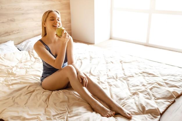 Młody Piękny Blondynki Kobiety Obsiadanie W łóżku W Ranku. Trzyma W Dłoni Duże Zielone Smaczne Jabłko I Patrzy Na To. Pozowanie Modelu. światło Dzienne. Premium Zdjęcia