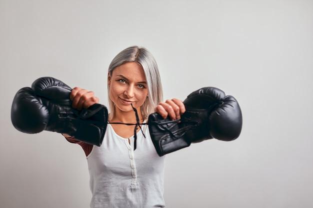 Młody Piękny Kobieta Bokser Pozuje Z Czarnymi Bokserskimi Rękawiczkami W Jej Rękach Na Szarości Premium Zdjęcia