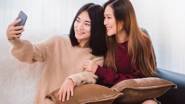Młody Piękny Kochanek Para Lesbijek Azjatyckich Za Pomocą Smartfona Selfie Razem W Salonie W Domu Z Uśmiechniętą Twarz. Koncepcja Seksualności Lgbt Ze Szczęśliwym Stylem życia Razem. Premium Zdjęcia