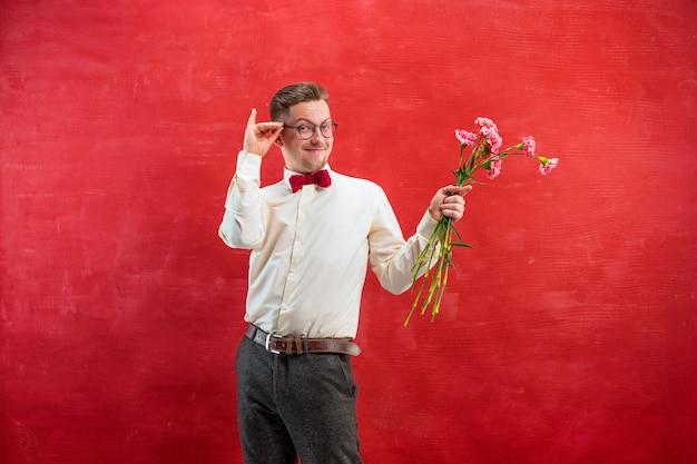 Młody Piękny Mężczyzna Z Kwiatami Na Czerwonym Tle Studio Darmowe Zdjęcia