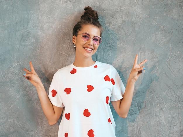 Młody Piękny Uśmiechnięty Kobiety Patrzeć. Modna Dziewczyna W Białej Letniej Sukience I Okularach Przeciwsłonecznych. . Pokazuje Znak Pokoju Darmowe Zdjęcia