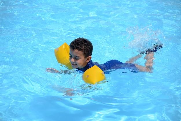 Młody Pływak, Chłopiec Pływanie W Wodzie Niebieski Basen Premium Zdjęcia
