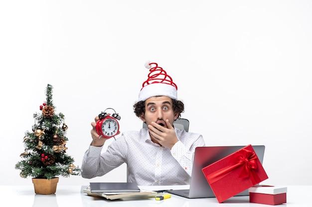 Młody Podekscytowany Zszokowany Biznesmen Z Czapką świętego Mikołaja I Pokazujący Zegar Pracujący Samotnie Siedzący W Biurze Na Białym Tle Darmowe Zdjęcia