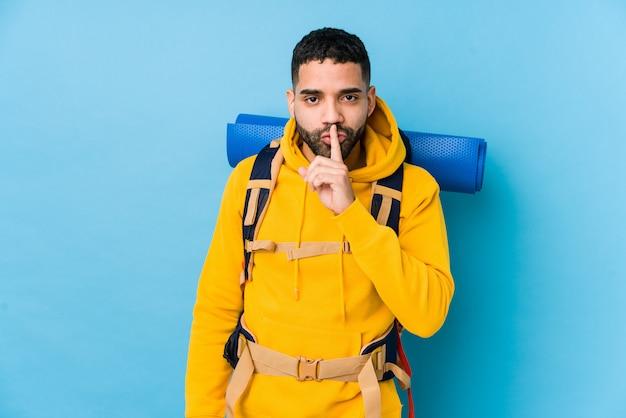 Młody Podróżnik Arabski Backpacker Mężczyzna Na Białym Tle Utrzymanie W Tajemnicy Lub Prosząc O Ciszę. Premium Zdjęcia