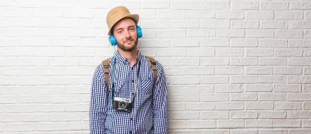 Młody podróżnik mężczyzna jest ubranym plecaka i rocznik kamerę pogodną iz dużym uśmiechem co Premium Zdjęcia