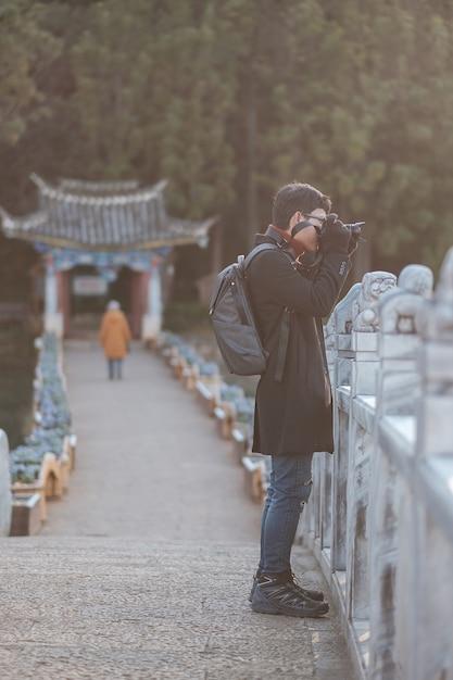 Młody Podróżnik Podróżujący W Basenie Black Dragon Z Jade Dragon Snow Mountain, Punktem Orientacyjnym I Popularnym Miejscem Atrakcji Turystycznych W Pobliżu Starego Miasta W Lijiang. Lijiang, Yunnan, Chiny Premium Zdjęcia
