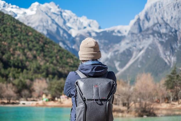 Młody Podróżnik Podróżujący W Dolinie Blue Moon, Charakterystycznym I Popularnym Miejscu W Jade Dragon Snow Mountain Mountain Scenic Area, Niedaleko Lijiang Old Town. Lijiang, Yunnan, Chiny. Koncepcja Podróży Solo Premium Zdjęcia