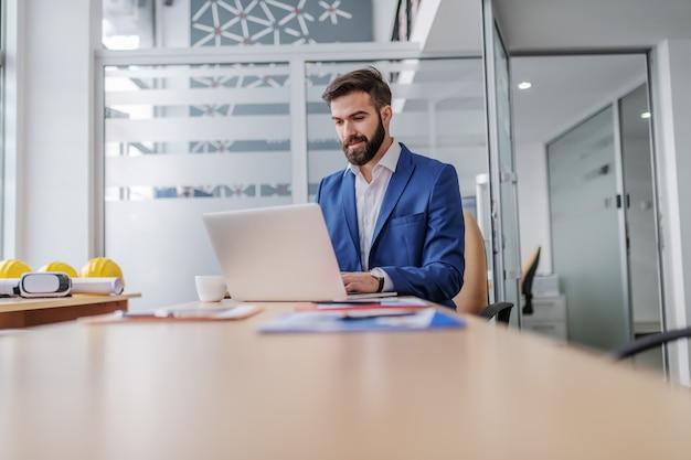 Młody Pracownik Rasy Brodaty Skoncentrowane Siedzi W Swoim Biurze I Za Pomocą Laptopa Do Pisania Raportu. Premium Zdjęcia