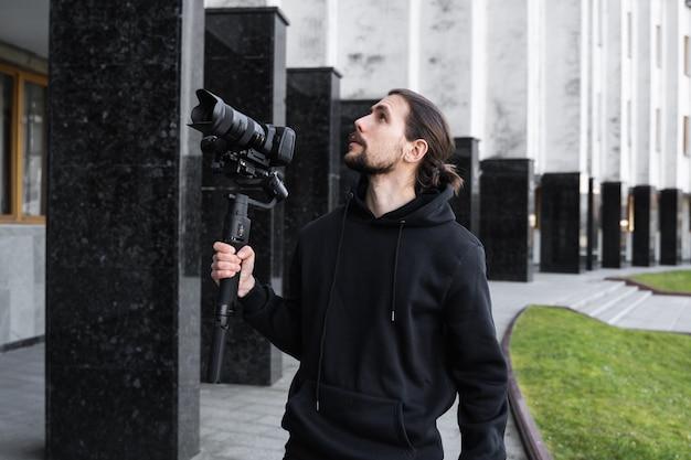 Młody Profesjonalny Kamerzysta Trzymający Profesjonalny Aparat Na 3-osiowym Stabilizatorze Gimbala. Profesjonalne Urządzenia Pomagają Tworzyć Wysokiej Jakości Filmy Bez Wstrząsania. Kamerzysta Ma Na Sobie Czarną Bluzę Z Kapturem I Nagrywa Filmy. Premium Zdjęcia