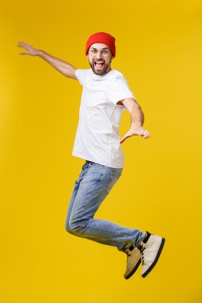 Młody Przypadkowy Człowiek Skaczący Z Radości Na żółtym Złocie Premium Zdjęcia