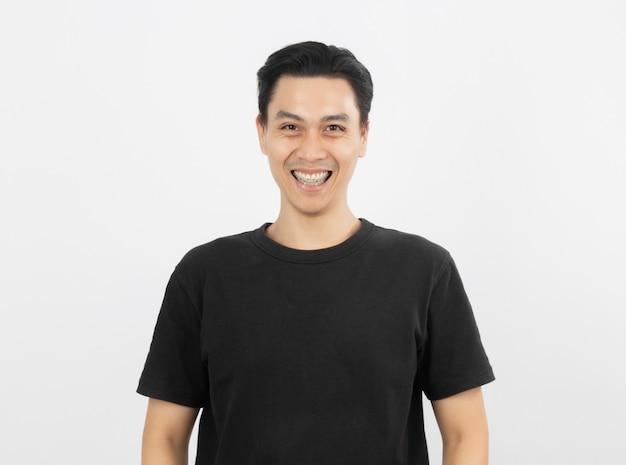 Młody przystojny azjatykci mężczyzna ono uśmiecha się z brasami i patrzeje kamerę Premium Zdjęcia