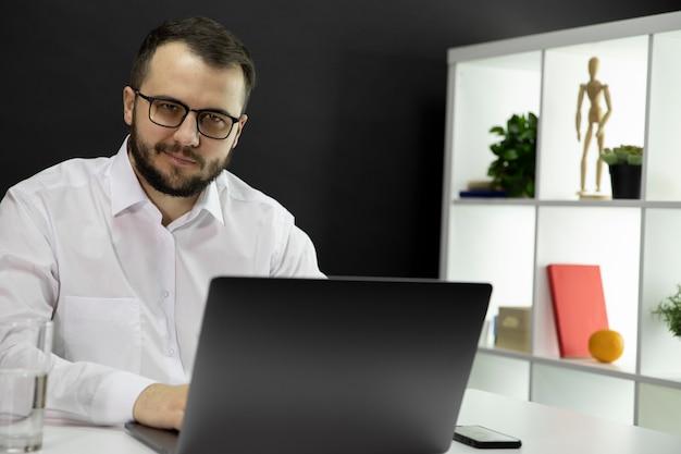 Młody Przystojny Biznesmen Pracuje Przy Komputerem W Ministerstwie Spraw Wewnętrznych. Uśmiechnięty Freelancer Premium Zdjęcia