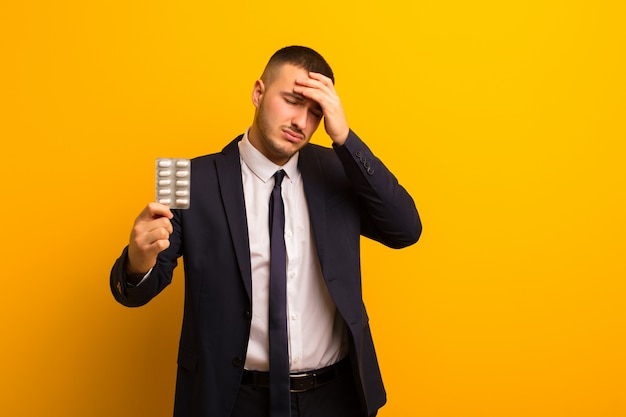 Młody Przystojny Biznesmen Przeciw Płaskiemu Tłu Z Pigułek Kapsułkami Premium Zdjęcia