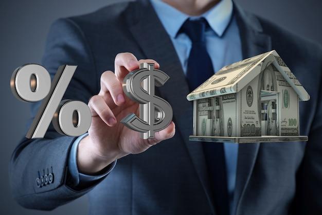 Młody przystojny biznesmen trzyma dom Premium Zdjęcia