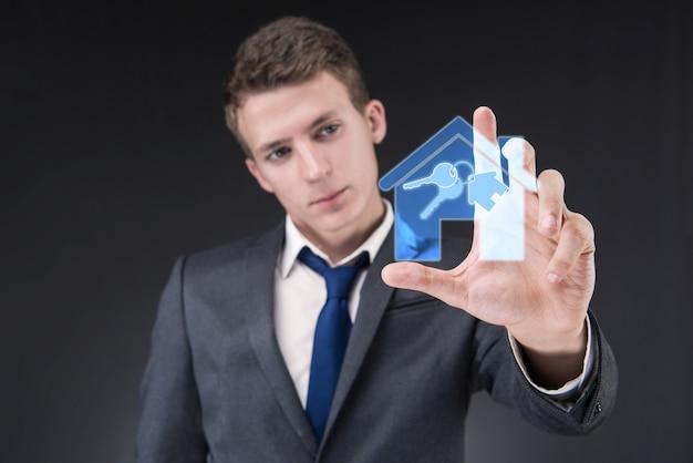 Młody przystojny biznesmen w hipotecznym pojęciu Premium Zdjęcia
