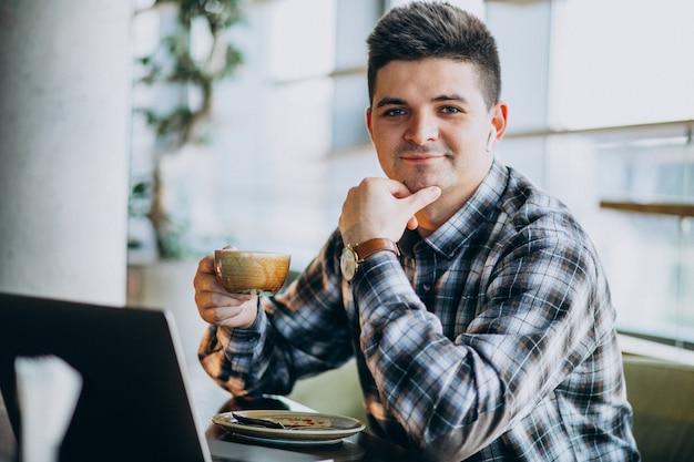 Młody Przystojny Biznesowy Mężczyzna Używa Laptop W Kawiarni Darmowe Zdjęcia
