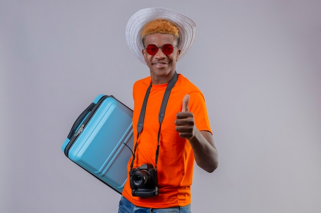Młody Przystojny Chłopak Podróżnik W Letnim Kapeluszu Na Sobie Pomarańczowy T-shirt, Trzymając Walizkę Podróżną Uśmiechnięty Przyjazny Pokazując Kciuki Do Góry Stojąc Nad Białą ścianą Darmowe Zdjęcia