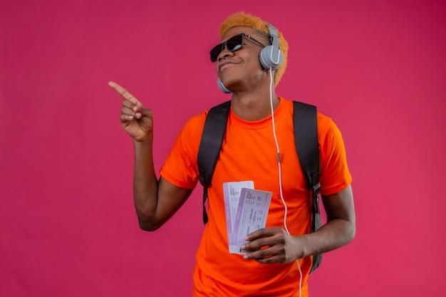Młody Przystojny Chłopak Z Plecakiem I Słuchawkami, Trzymając Bilety Lotnicze, Wskazując Palcem Na Bok, Ciesząc Się Ulubioną Muzyką Darmowe Zdjęcia