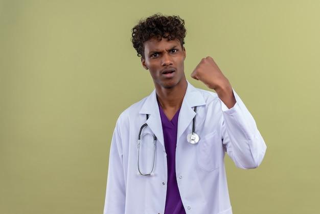Młody Przystojny Ciemnoskóry Lekarz Z Kręconymi Włosami W Białym Fartuchu Ze Stetoskopem Z Agresywnym Wyrazem Twarzy Pokazujący Zaciśniętą Pięść Na Zielonej Przestrzeni Darmowe Zdjęcia