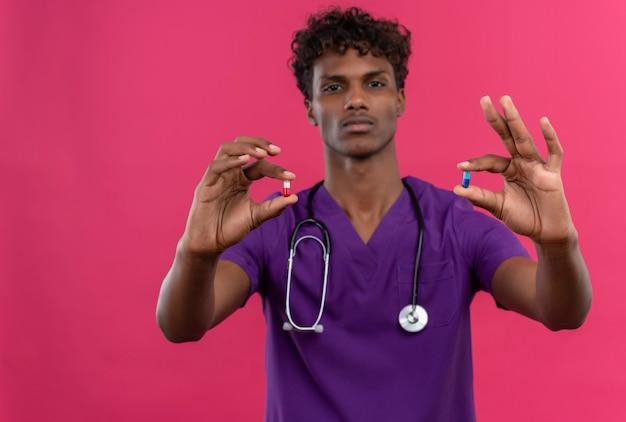 Młody Przystojny Ciemnoskóry Lekarz Z Kręconymi Włosami W Fioletowym Mundurze Ze Stetoskopem Pokazującym Tabletki Darmowe Zdjęcia