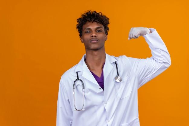 Młody Przystojny Ciemnoskóry Mężczyzna Z Kręconymi Włosami, Ubrany W Biały Fartuch Ze Stetoskopem, Podnosząc Rękę Z Zaciśniętą Pięścią Darmowe Zdjęcia