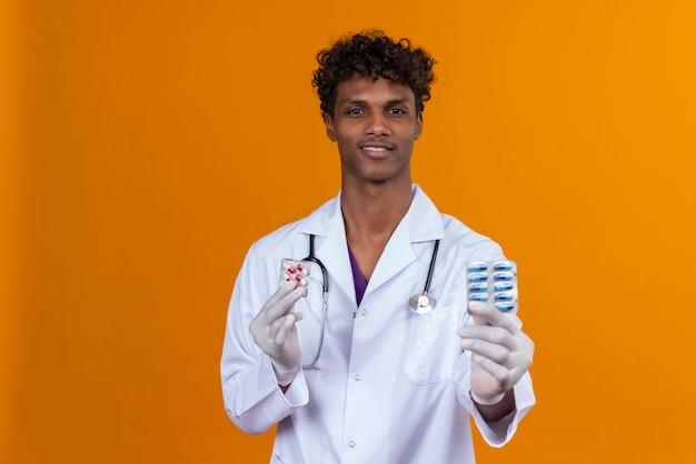 Młody Przystojny Ciemnoskóry Mężczyzna Z Kręconymi Włosami W Białym Fartuchu Ze Stetoskopem Przedstawiającym Tabletki Darmowe Zdjęcia