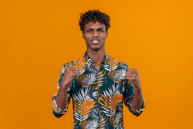 Młody Przystojny Ciemnoskóry Mężczyzna Z Kręconymi Włosami W Koszulce Z Nadrukiem Liści Z Wściekłą Twarzą Trzymającą Się Za Ręce Z Zaciśniętymi Pięściami Darmowe Zdjęcia