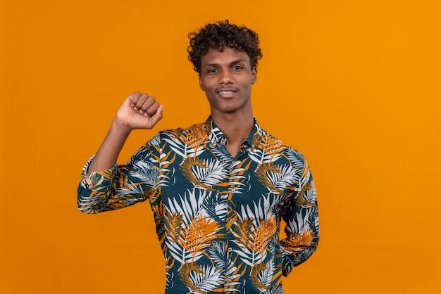 Młody Przystojny Ciemnoskóry Mężczyzna Z Kręconymi Włosami W Koszulce Z Nadrukiem W Liście, Uśmiechnięty, Podnoszący Dłoń Z Zaciśniętą Pięścią Darmowe Zdjęcia
