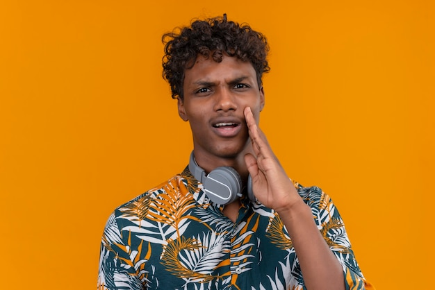 Młody Przystojny Ciemnoskóry Mężczyzna Z Kręconymi Włosami W Koszulce Z Nadrukiem W Liście Z Agresywną Twarzą Wzywający Kogoś Trzymającego Rękę Na Twarzy Darmowe Zdjęcia