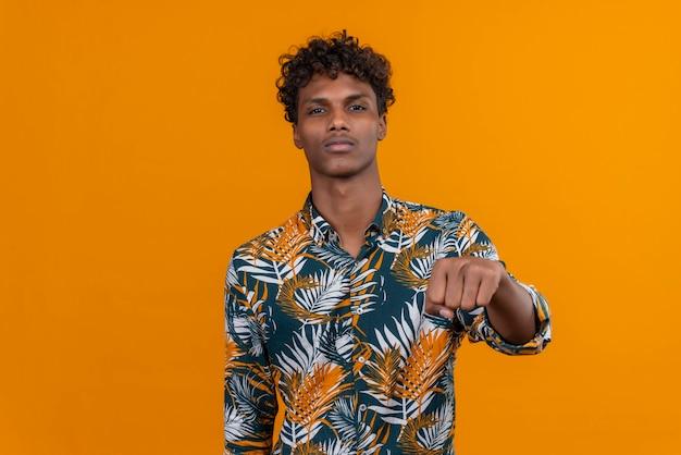 Młody Przystojny Ciemnoskóry Mężczyzna Z Kręconymi Włosami W Koszuli Z Nadrukiem Liści, Wskazując Na Aparat Z Zaciśniętą Pięścią Darmowe Zdjęcia