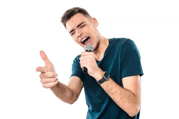 Młody przystojny facet śpiewa karaoke ekspresyjnie Premium Zdjęcia