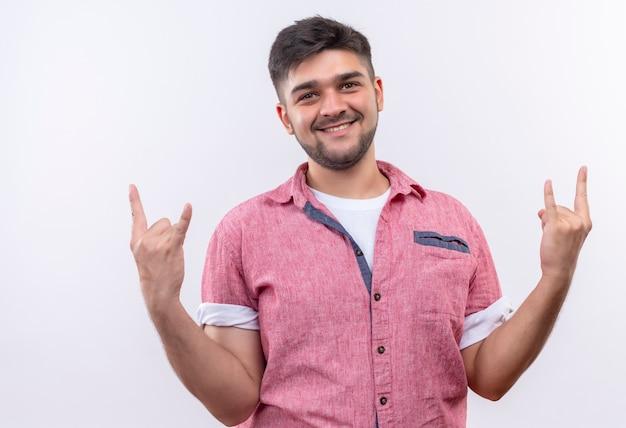 Młody Przystojny Facet Ubrany W Różową Koszulkę Polo Robi Rocka Na Zawsze Znak Palcami Patrząc Szczęśliwie Stojąc Na Białej ścianie Darmowe Zdjęcia