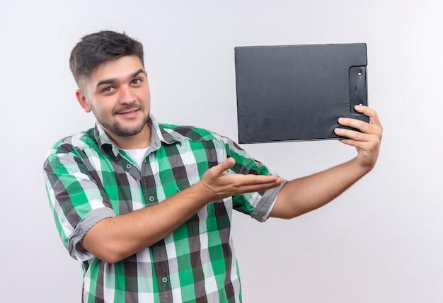 Młody Przystojny Facet W Kraciastej Koszuli Próbuje Sprzedać Schowek Stojący Nad Białą ścianą Darmowe Zdjęcia