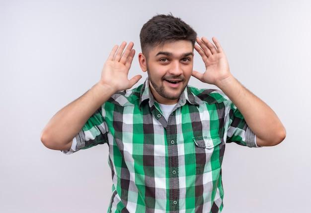 Młody Przystojny Facet W Kraciastej Koszuli Próbuje Usłyszeć Stojącego Nad Białą ścianą Darmowe Zdjęcia