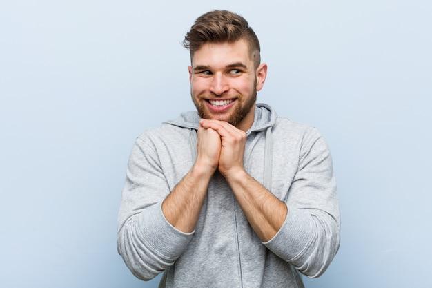 Młody Przystojny Fitness Mężczyzna Trzyma Ręce Pod Brodą, Patrzy Szczęśliwie Na Bok. Premium Zdjęcia