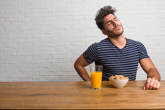 Młody przystojny i naturalny mężczyzna obsiadanie na stole z bólem pleców z powodu praca stresu Premium Zdjęcia