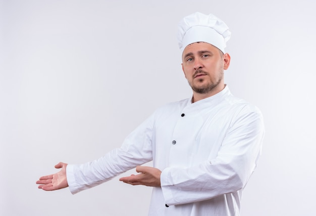 Młody Przystojny Kucharz W Mundurze Szefa Kuchni, Wskazując Rękami Na Boku, Patrząc Na Białym Tle Na Białej Przestrzeni Darmowe Zdjęcia