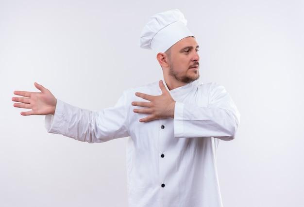 Młody Przystojny Kucharz W Mundurze Szefa Kuchni, Wskazując Rękami Po Lewej Stronie I Patrząc Na Bok Na Na Białym Tle Darmowe Zdjęcia