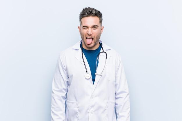 Młody przystojny lekarz mężczyzna zabawny i przyjazny wystaje język. Premium Zdjęcia