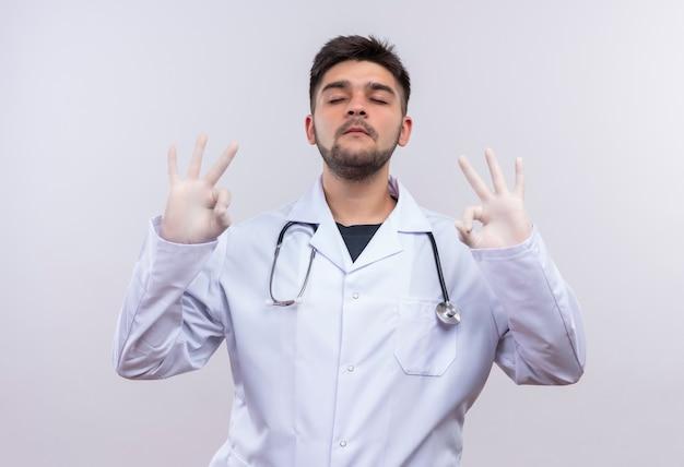 Młody Przystojny Lekarz Ubrany W Białą Suknię Medyczną Białe Rękawiczki Medyczne I Stetoskop Próbuje Się Uspokoić Pokazując Znak Ok Z Rękami Zamkniętymi Oczy Stojąc Nad Białą ścianą Darmowe Zdjęcia