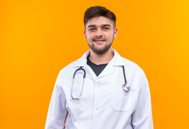 Młody Przystojny Lekarz Ubrany W Białą Suknię Medyczną Białe Rękawiczki Medyczne I Stetoskop Uśmiechnięty Stojący Nad Pomarańczową ścianą Darmowe Zdjęcia