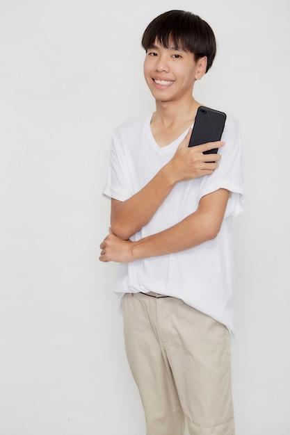 Młody Przystojny Mężczyzna Azjatyckich Posiadania Telefonu Komórkowego Na Tle Białego Studia Premium Zdjęcia