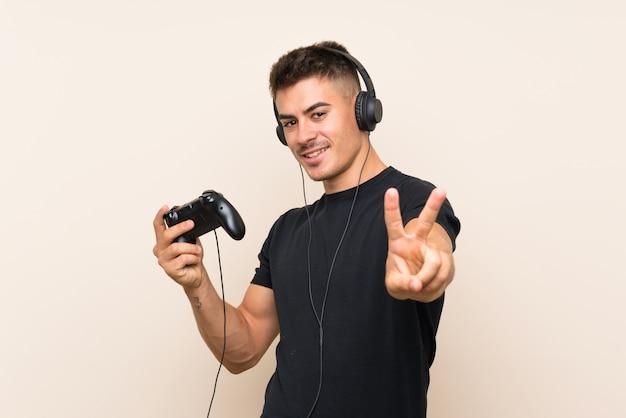 Młody Przystojny Mężczyzna Bawić Się Z Kontrolerem Gier Wideo Uśmiecha Się Znak Zwycięstwa I Pokazuje Premium Zdjęcia