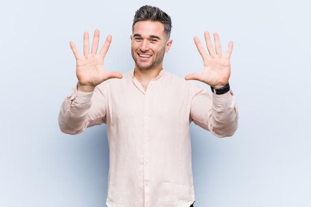 Młody przystojny mężczyzna fajne wyświetlono numer dziesięć rękami. Premium Zdjęcia