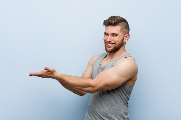 Młody Przystojny Mężczyzna Fitness Posiadający Miejsce Na Kopię Na Dłoni. Premium Zdjęcia