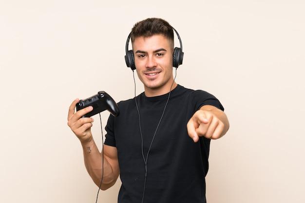 Młody przystojny mężczyzna, grając z kontrolerem gier wideo nad izolowanymi punktami na ścianie, palcem do siebie z pewnym siebie wyrazem twarzy Premium Zdjęcia